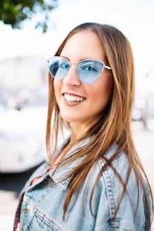 Крупным планом портрет стильной улыбкой счастливой молодой женщины на улице с идеально белыми зубами