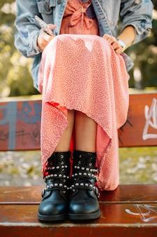ストラップ、メタルスタッド、ジッパーの女性の黒革アンクルブーツは、路上で落書きのあるベンチで撮影しました。