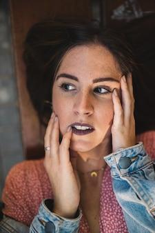 アクセサリー、ゴールデンムーンネックレス、イヤリング、完璧な白い歯と木製のベンチに横になっている手で彼女の顔に触れる女性の肖像画を閉じます。美しさとファッション。化粧品とスキンケア。