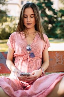 携帯を見てベンチに座っているピンクのドレスで幸せな若い女。良いニュースを持っている女性。幻想の女性