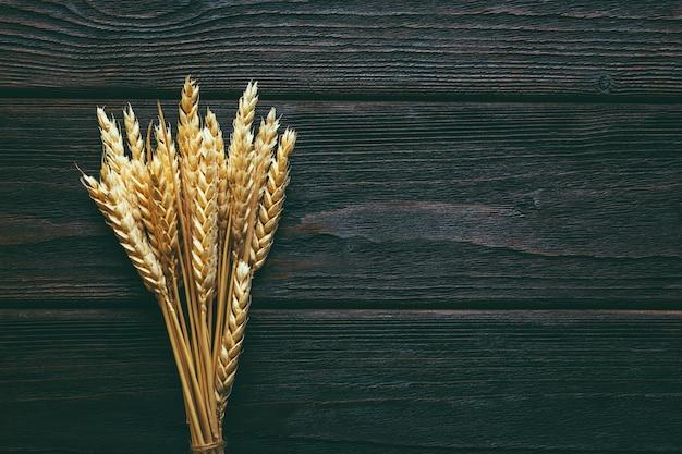 Колоски пшеницы на темной деревянной поверхности