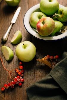暗い木製のテーブルの上の秋のリンゴ