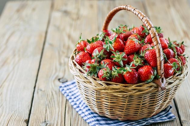 木製の背景上のバスケットに新鮮な熟したイチゴ