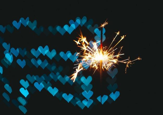 Горящий бенгальский огонь в спине - это боке в форме сердца. концепция знаменитостей. пространство для текста
