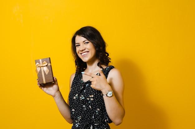 ギフト用の箱を開き、黄色の壁に孤立したジェスチャーを示す幸せな笑顔の女の子の画像