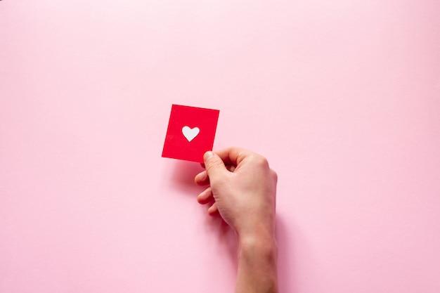 Рука держит сердце над розовой стеной, день святого валентина. плоская планировка