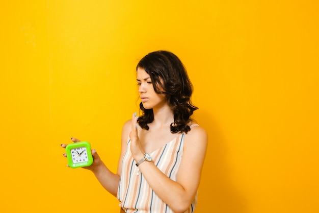 Портрет брюнетки, отчаянно нуждающейся в ежедневной тревоге на желтой стене