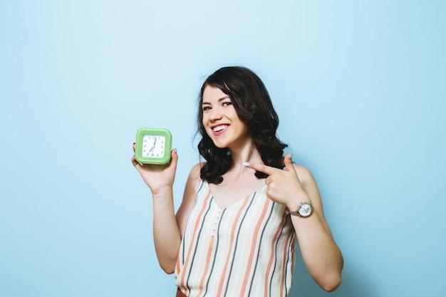 目覚まし時計を保持している青い壁に分離された若い幸せな女性の肖像画。