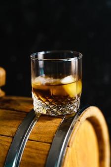 木製の樽の上に座ってウイスキーのグラス