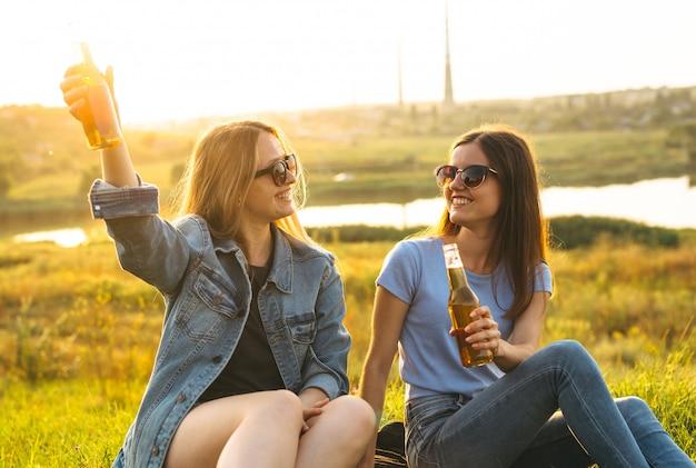 Две веселые девушки и молодые друзья с очками, пили пиво и наслаждались временем, проведенным вместе на закате.
