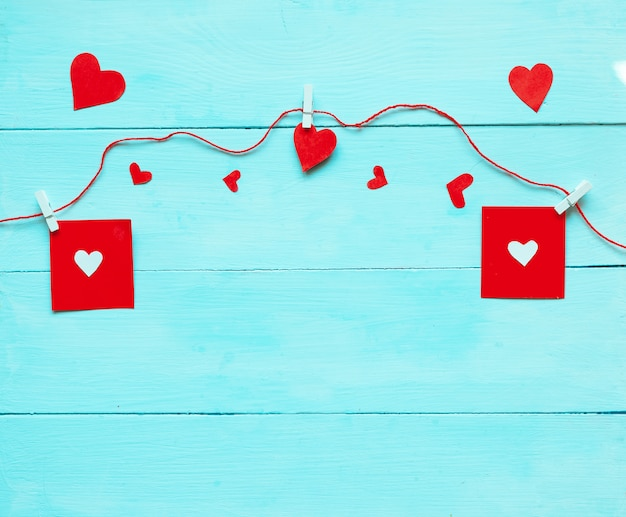 赤いハートと青い背景上のアクセサリーとバレンタインデーの背景。フラット横たわっていた、トップビュー!