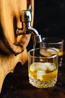 木製の樽とウイスキーのグラス。