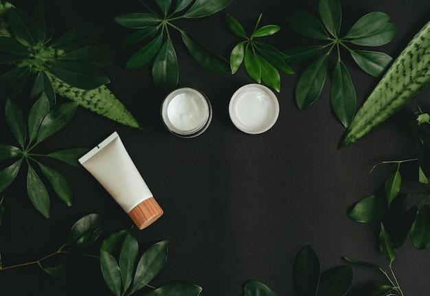 自然化粧品と黒いテーブルの上の緑の葉。