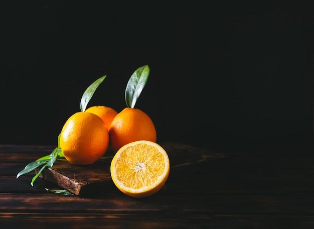 Плоды апельсина как целые, так и нарезанные на деревенский деревянный стол