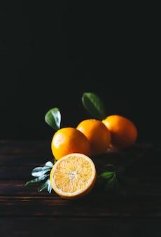 Плоды апельсина как целые, так и нарезанные на деревенском деревянном столе в винтажном стиле
