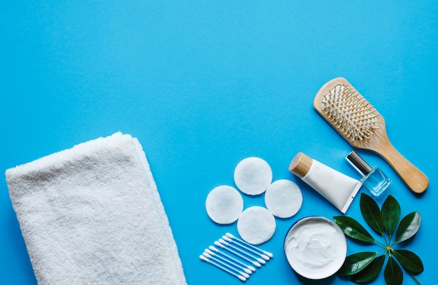 トップビューのパステルブルーのテーブルで毎日の衛生とスキンケアのための製品。自然化粧品。