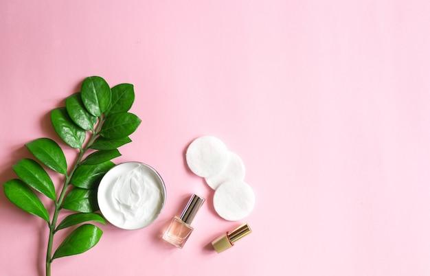 トップビューのパステルピンクのテーブルでの自然化粧品と毎日の衛生