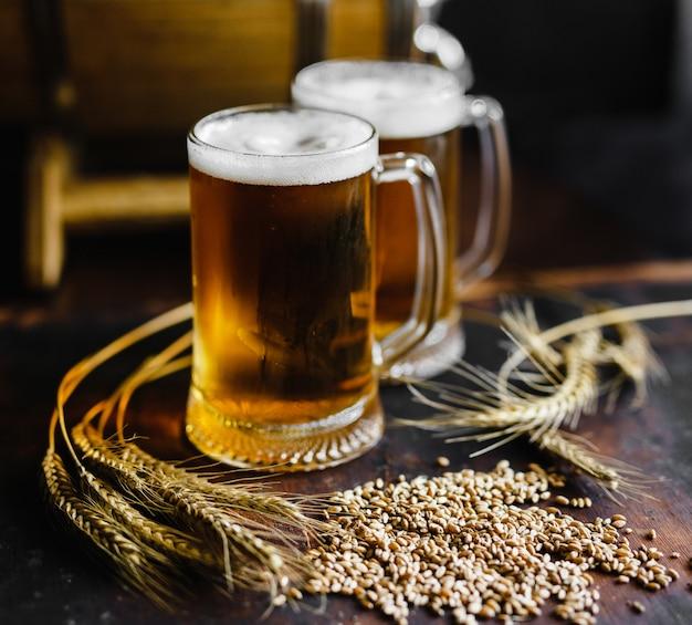 ビールのグラスと黒の背景に古い素朴な木製のテーブルに小麦のスパイス