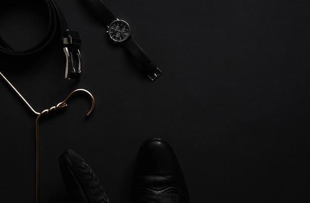 ゴールデンハンガー、黒いベルト、黒いテーブルの腕時計。メンズアクセサリーと美容機器。