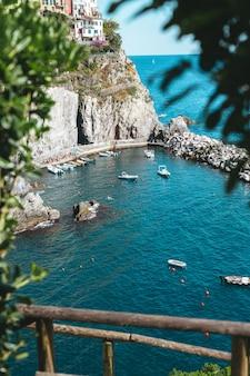 イタリアのチンクエテッレ国立公園の海岸近くの青い水のボート