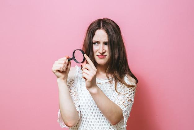 虫眼鏡を通して見る若い女性