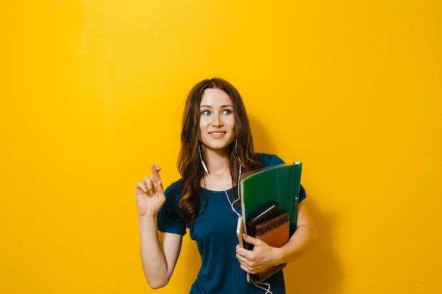 本や学用品を保持している美しい少女若い学生の肖像画