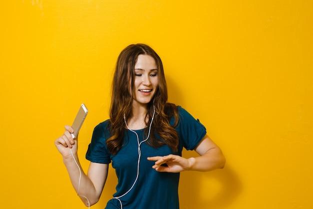 携帯電話を保持していると、イヤホンで音楽を聞いて美しい少女