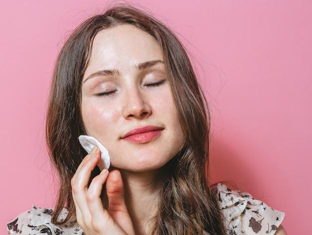 綿のパッドで顔を掃除する若いブルネットの女性の肖像画