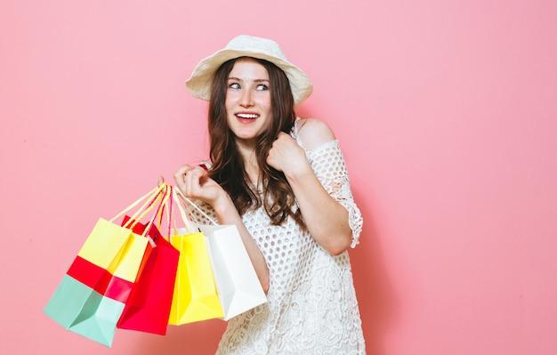 ピンクの買い物袋を保持している笑顔の陽気な女の子の画像