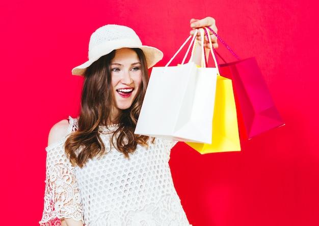 買い物袋を押しながら赤でクレジットカードを示す笑みを浮かべて陽気な少女の肖像画