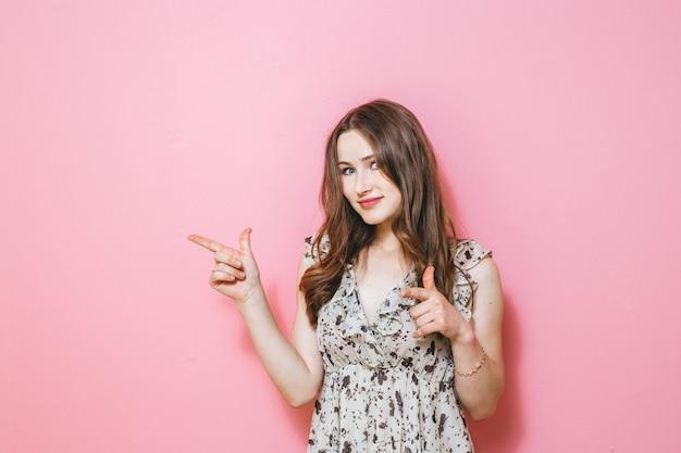 ピンクの上にジェスチャーを提示する興奮した女性の画像