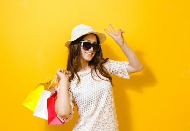 黄色の上の買い物袋を保持している笑顔の陽気な少女の肖像画