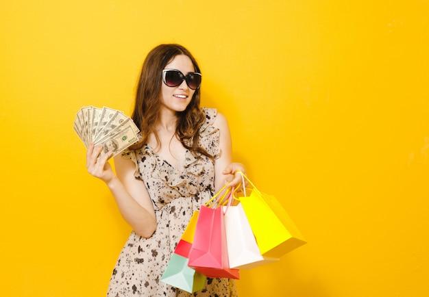 黄色で分離された買い物袋を保持しているサングラスと興奮して美しい少女の肖像画