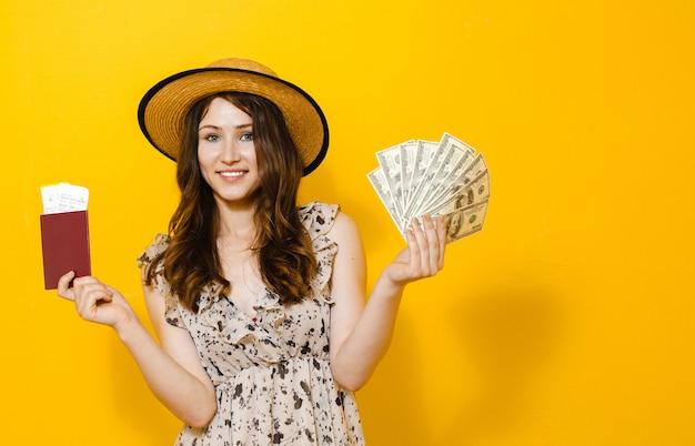 お金紙幣を保持している美しい幸せなブルネットの少女の肖像旅行チケットとパスポート