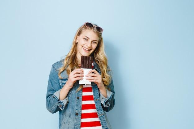 チョコレートを食べる美しいブロンドの女の子は青色の背景に興奮しています。