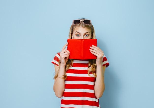 青い背景に赤いカードで彼女の目を隠して美しいブロンドの女の子