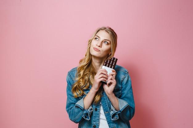 チョコレートを食べて美しいブロンドの女性の肖像画は興奮しています。