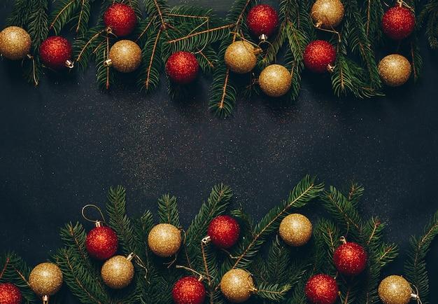 Концепция рождества на черной предпосылке с игрушками и зеленой елью.