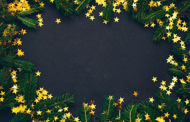 Зеленая ель с елочные игрушки и черный фон. рождественская концепция плоская планировка, вид сверху