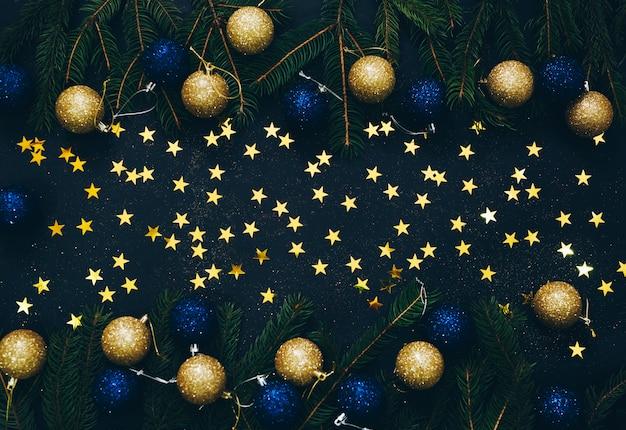 空のスペースで黒の背景に緑のモミとクリスマスのおもちゃのフレーム。フラット横たわっていた。上面図