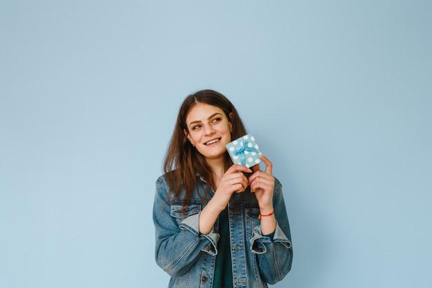 Портрет возбужденных молодая красивая девушка держит подарок и счастливым на синем фоне
