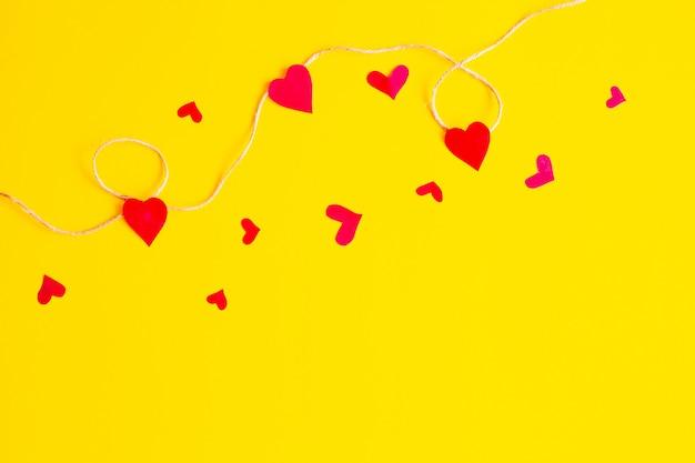 Предпосылка дня валентинки с красными сердцами и аксессуарами над желтой предпосылкой. предпосылка форм влюбленности. плоская планировка, вид сверху!