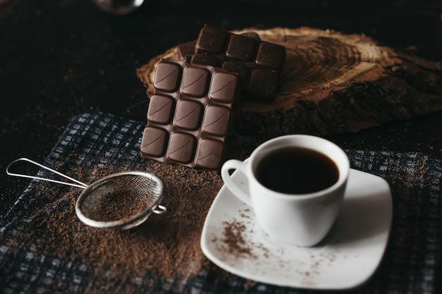 素朴なテーブルにコーヒーとクルミのカーネルとダークチョコレート