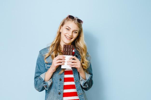 チョコレートを食べる美しいブロンドの女の子の肖像画は、青色の背景に興奮しています。