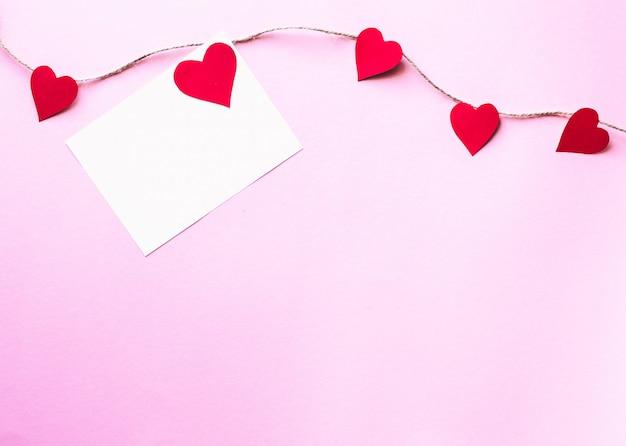 ピンクの背景のバレンタインデーのコンセプトに紙の心