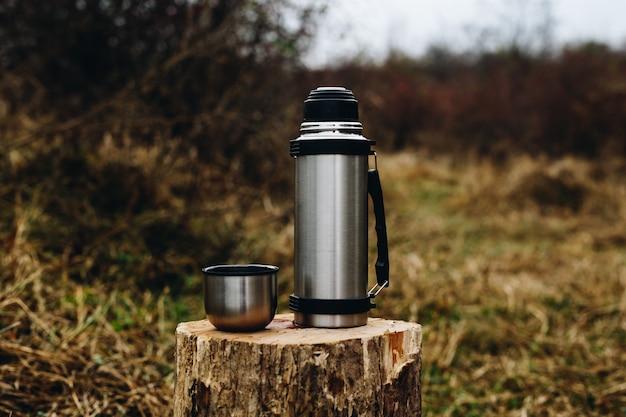 森の中の木の丸太の上に立って魔法瓶。テキスト用のスペース