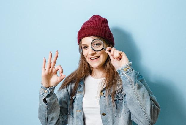 Портрет брюнетка девушка держит увеличительное стекло