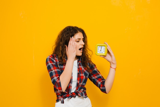 Изображение шокирован молодая женщина, изолированные над желтой стеной, показывая будильник