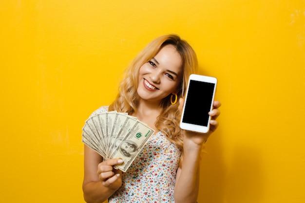 黄色の背景に電話と紙幣を保持している若い幸せな美しいブロンドの女の子の肖像画