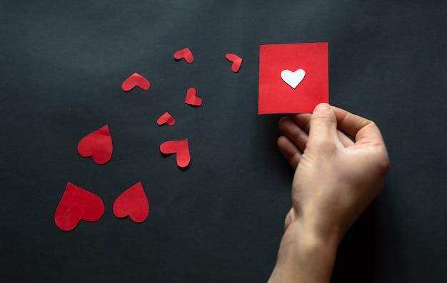 バレンタインの日、黒の背景に黒の心を持っている手。フラットレイ